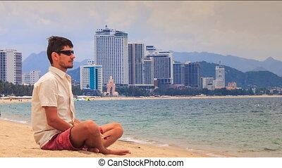 guy in sunglasses operates iphone sitting on sand beach -...