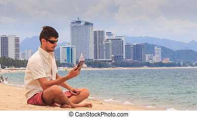 guy in sunglasses checks message in iphone sitting on sand...