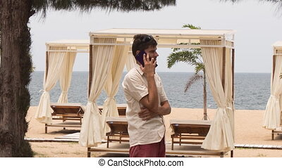 guy speaks over phone on beach against sunbeds under tents -...