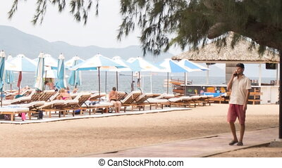 guy walks speaks on phone on beach against sunbeds umbrellas...