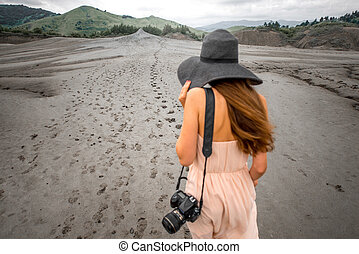 Female traveler walking near mud volcanoes - Young female...