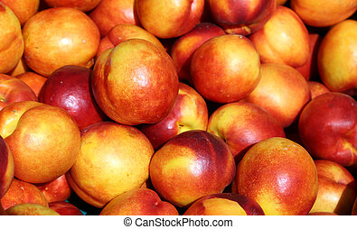 ripe nectarines background for sale at vegetable market in...