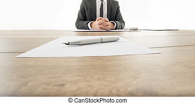 Businessman sitting at his wooden office desk with contract infront of him and another contract opposite to him