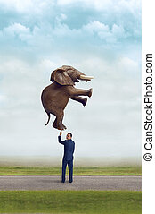 businessman holding an elephant with one finger subtle...