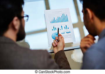 Market increase - Businessman explaining chart in document...