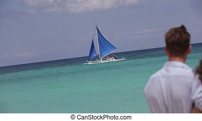 Young couple looks at the sailboat.
