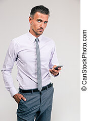 Handsome businessman using smartphone - Portrait of a...