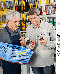 Salesperson Assisting Customer In Buying Pliers - Senior...