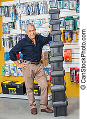 Senior Man Standing By Stacked Toolboxes In Shop - Full...