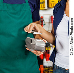 Customer Paying With Smartphone Using NFC - Female customer...