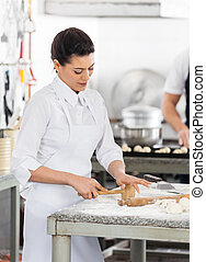 Chef Shaping Pasta At Counter In Kitchen