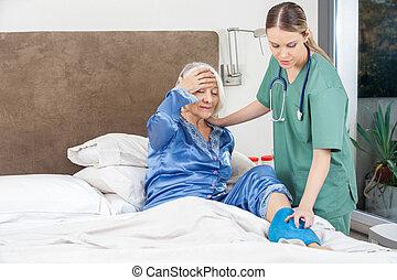 Caretaker Using Hot Water Bag On Senior Woman - Female...