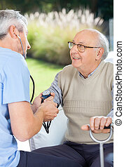 Male Doctor Measuring Blood Pressure Of Elderly Man - Male...