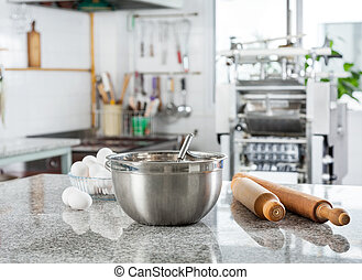 Bowl With Eggs And Rolling Pin In Commercial Kitchen -...