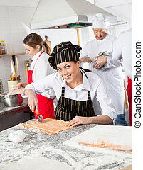 Smiling Female Chef Cutting Ravioli Pasta At Counter -...