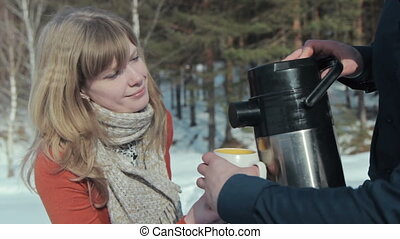 Young pair in wood. Man pours tea from a thermos. - Young...