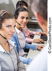 Customer Service Agents Looking At Manager - Young female...