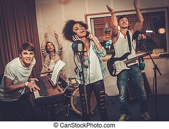 Multiracial music band performing in a recording studio