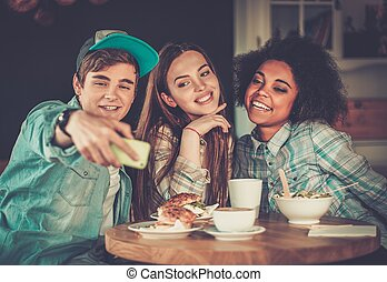 Cheerful multiracial friends taking selfie in a cafe