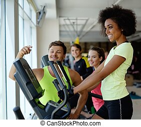 Trainer explaining how to use elliptical training machine