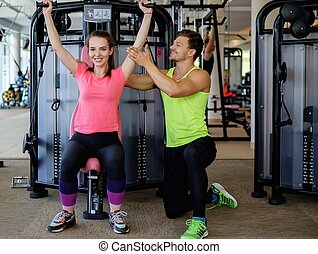 Trainer explaining how to use training machine in a gym