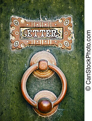 Letters - An old letterbox and doorknocker on a green door...