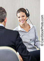 Young Female Customer Service Executive Looking At Manager -...