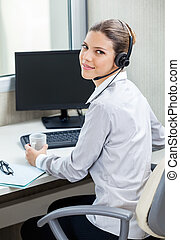 Customer Service Agent At Computer Desk - Portrait of young...