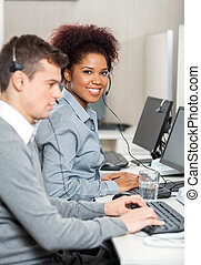 Young Employee With Male Colleague Working In Office -...