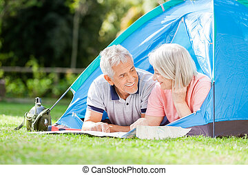 Senior Couple Studying Map In Tent At Park - Senior couple...