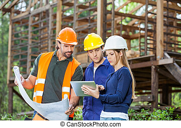 Engineers Using Digital Tablet At Construction Site