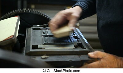 brushing letterpress type in a chase - printer cleans off...