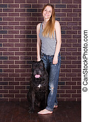 girl standing near the wall and hugging a big dog Cane Corso