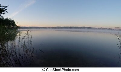 Beautiful landscape - morning haze spreads across the lake...
