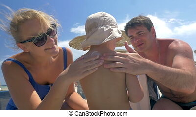 Parents applying suntan lotion on childs skin - Slow motion...