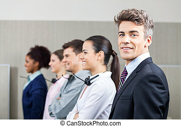 Smiling Manager Standing In Row With Team - Portrait of...