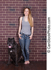 girl in jeans and shirt standing  hugging a big dog Cane Corso