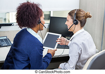 Smiling Call Center Employees Discussing While Using Digital...