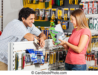 Couple With Cordless Drill In Store - Playful couple with...