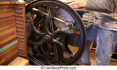 letterpress flywheel - a printer operates a manual...