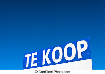 Large Dutch for sale sign in front of a blue sky