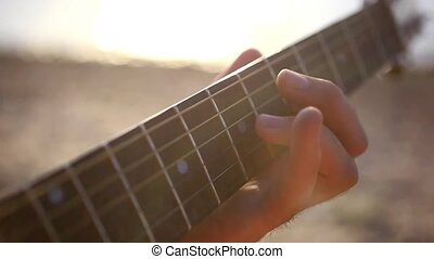 Fingers musician playing guitar in the beach during sunset...