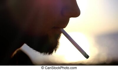 Face of brutal bearded musician smoking a cigarette on the...