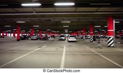 Parking garage, underground interior with a few parked cars...