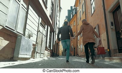 Happy Couple Running along the Narrow Street - Steadicam...