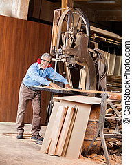 Happy Senior Carpenter Using Bandsaw - Full length portrait...