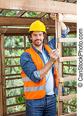Portrait Of Construction Worker Measuring Timber Frame