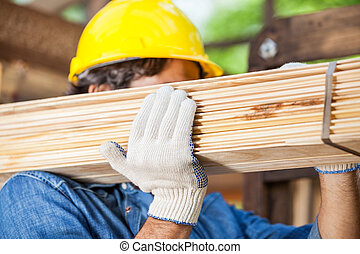Worker Carrying Tied Wooden Planks At Construction Site -...