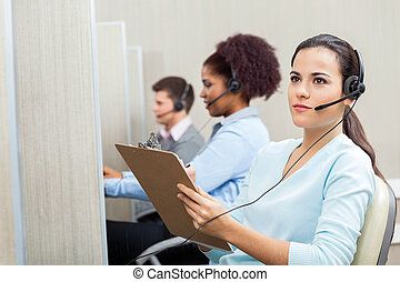 Thoughtful Female Customer Service Agent Holding Clipboard -...
