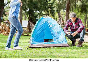 Woman Walking By Man Preparing Tent In Park